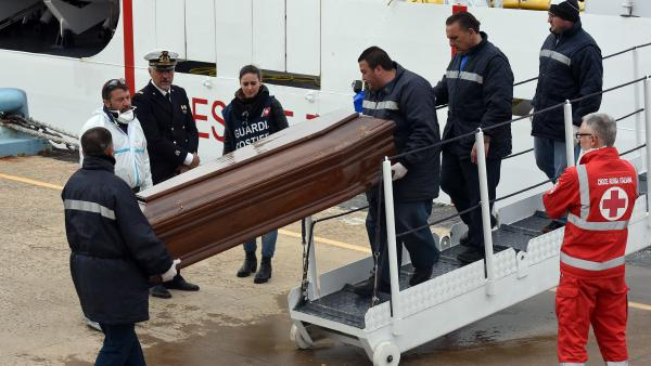 """Men carry a coffin during the arrival of migrants and refugees in the port of Messina following a rescue operation at sea by the Italian Coast Guard ship """"Diciotti"""" on March 17 in Sicily. After several quiet weeks, March saw a pickup in the flow of migrants attempting to reach Italy via Libya, a route through which about 330,000 people have made it to Europe since the start of 2014."""