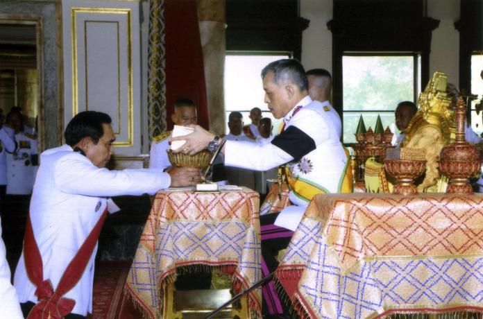 El Rey Vajiralongkorn Bodindradebayavarangkun (derecha) firma la nueva constitución de la junta durante la ceremonia junto al Primer Ministro y líder de la junta Prayuth Chan-ocha (izquierda)   Fuente: Associated Press