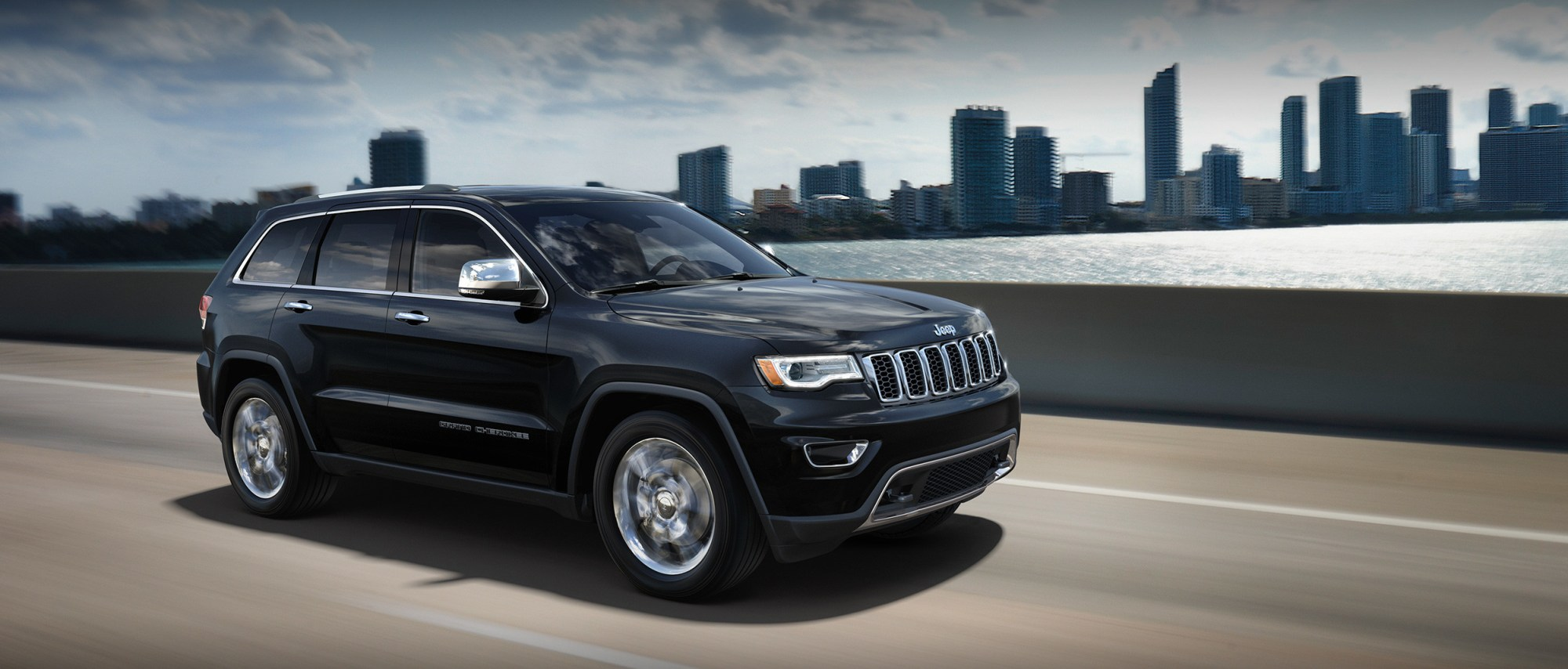 hight resolution of  black 2019 jeep grand cherokee speeding through the roads in front of a city skyline