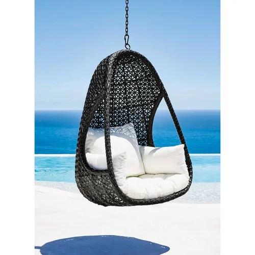 fauteuil suspendu de jardin en resine tressee noire et coussins blancs maisons du monde
