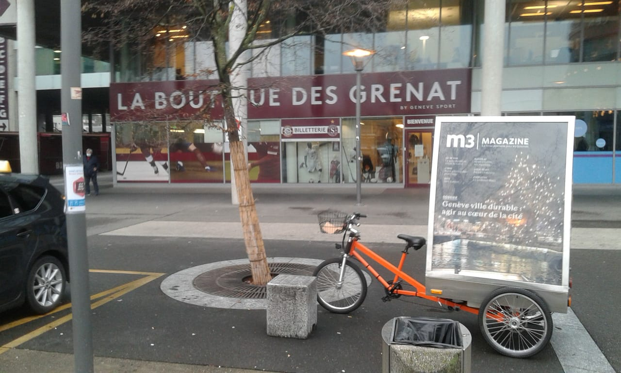 Vélo publicitaire électrique MediaShift avec une affiche m3 magazine devant les locaux de m3 GROUPE