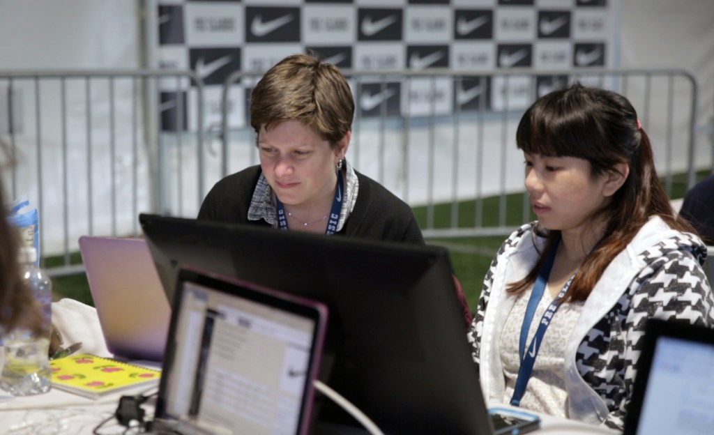 University of Oregon student Romaine Soh waits as journalism instructor Lori Shontz edits her story at the Prefontaine Classic. Photo by Charlie Litchfield, University of Oregon