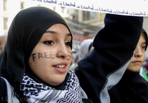 "A young woman with the words ""Free Syria"" written on her face attends a demonstration against violence in Syria on February 26, 2012 in Madrid. Photo by Freedom House on Flickr and used here with Creative Commons license."
