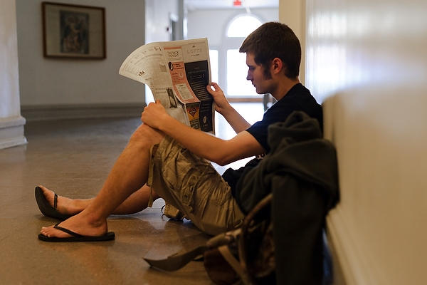 An undergraduate in a quiet corner of a Bascom Hall hallway at the University of Wisconsin-Madison reads the Badger Herald student newspaper while waiting for his next class to start. (Photo by Jeff Miller courtesy of UW-Madison University Communications)