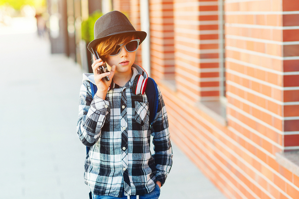 Young teenager walking outside and using his phone.