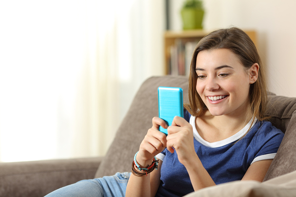 Teen looking at a smartphone with a blue case