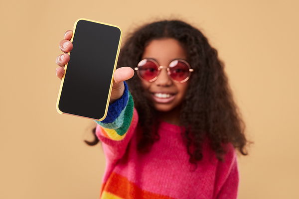 Young teen holding up her phone.