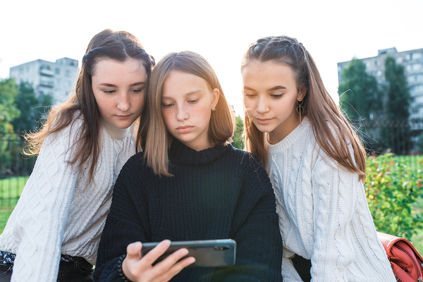 Three young teens looking at a phone together outside.