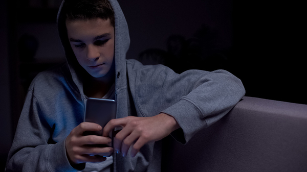 Teen sitting down looking at his phone screen.