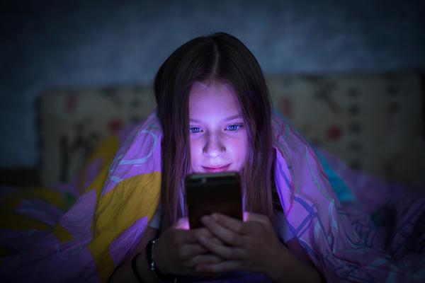 Teenage girl lying down in the dark looking at her smartphone.