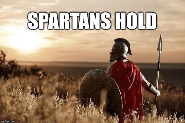 Spartański wojownik trzyma tarczę i broń.