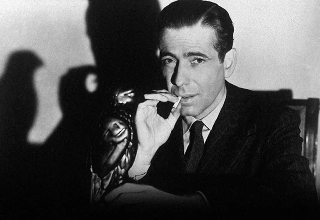Humphrey Bogart holding black Maltese Falcon statue.