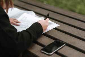 woman taking notes in text near mobile phone