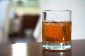 half-full glass of amber-colored beverage