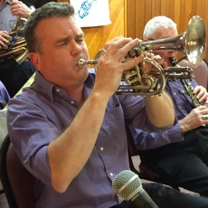 Travel editor Spud Hilton blows his own horn monthly with the Joyful Noise Jazz Band in El Sobrante.  The hot air goes in the skinny end and the metal thing transforms it into the joyful noise.  Copy isn't all that Spud makes sing.