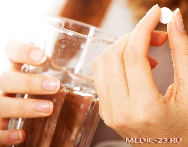 Женщина запивает таблетку водой