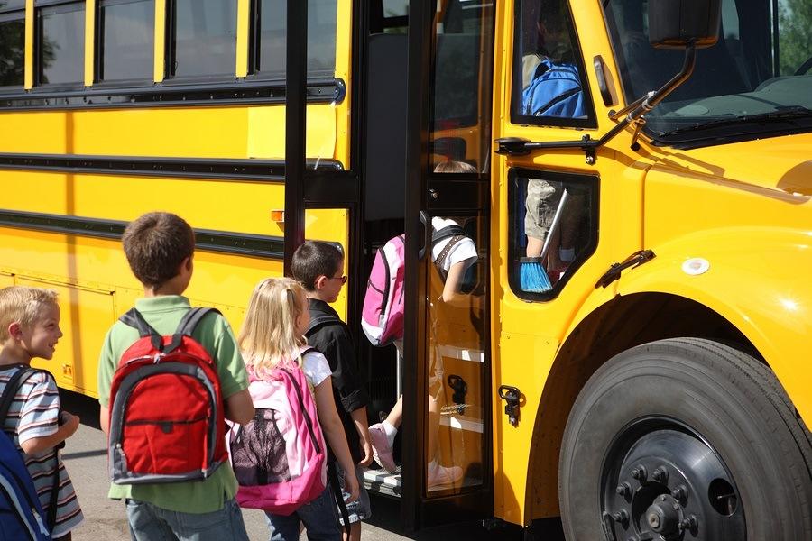Elementary school students getting on school bus