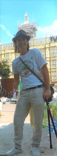 Medical cannabis protestor holding cannabis plant outside Houses of Parliament in London