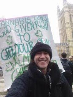British cannabis marijuana protestor, standing with sign outside British Parliament.