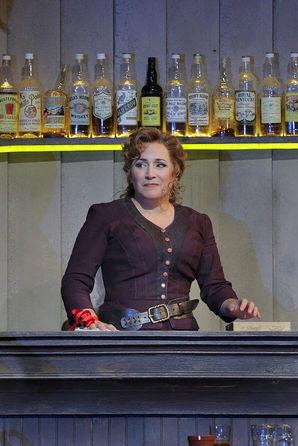 Minnie (Racette) behind the bar