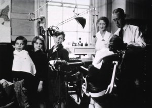 View of a dentist, a nurse, and four children, one of whom is sitting in the dental chair in the office.