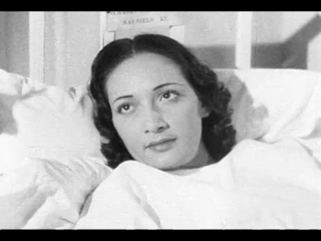 A dark-haired woman lies in a hospital bed.