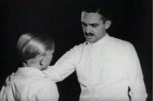 The dentist speaks to a boy, putting his hand on his shoulder.