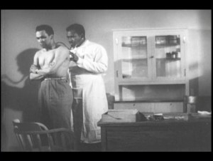A black doctor examines a black man with a stethescope.