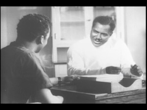 A black doctor sits at a desk and speaks to a black patient.