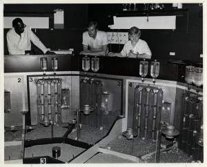 Dr. Calhoun and his colleagues are seated at a counter that surrounds the mouse universe, several feet off the floor of the enclosure. Dr. Calhoun has a pen in his left hand and an open notebook in front of him.