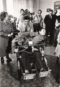 In a crowded room with TV cameras, a man poses with Masha and Dasha, as adults, in a specially designed wheelchair.