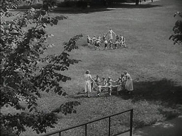 Children play ring-around-the rosy in a sunny grass area.