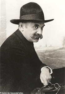 A mustachioed man in a black fedora poses informally..