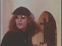 A man with long hair, oval sunglasses, and a black beret holds a cigarette.