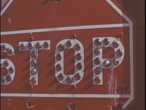 A red sign with STOP printed on it, electric light bulbs trace each letter.