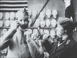 A woman reaches to ward a man in uniform as he adjusts a facial prosthetic.
