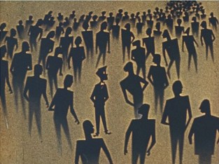 Rodney stands in a crowd of people all in silhouette.