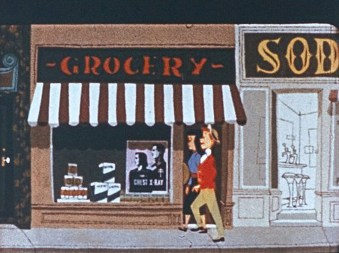 Rodney and his girlfriend walking on the sidewalk, in front of a grocery store that has a tuberculosis prevention poster in the window.