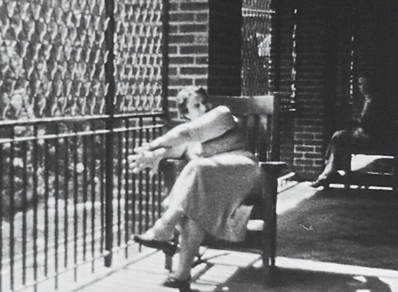 A woman in a chair makes large gestures on a porch in a chain-link enclosure.