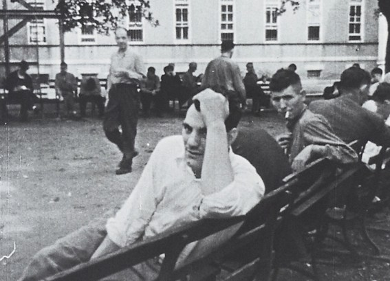 A group of men on benches on the grounds of a large building.