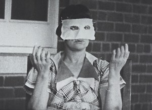 A masked woman patient sits in front of a brick wall next to a window makes hand gestures.