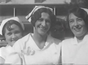 TB nurses in white uniforms with nursing caps smile for the camera