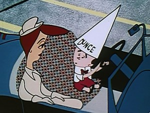 Ed Parmalee, behind the wheel of his car and sitting next to his wife, is turned into a little boy wearing a dunce cap.