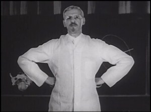 Film still of DeLee in a white coat standing akimbo.