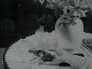 A revolver laying in an open hand next to bottles labeled Paxton's Panacea.