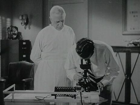 Men in scrubs use a microscope.