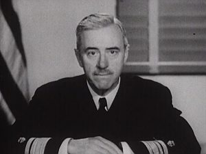 A man in uniform formally addresses the camera.