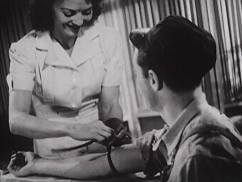 A nurse takes blood from a serviceman.