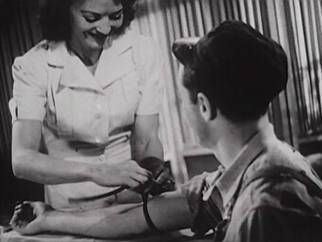 A nurse takes blood from a serviceman.