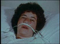 A young person in a hospital bed with breathing tubes.